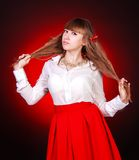 De mooie jonge vrouw in een wit chemise en een rode rok stock fotografie