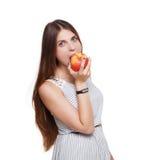 De mooie jonge vrouw eet grote rode die appel op wit wordt geïsoleerd Stock Afbeelding