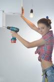 De mooie jonge vrouw gebruikt een elektrische boor Royalty-vrije Stock Foto