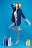 De mooie jonge vrouw in glazen en in een hoed houdt vele pakketten op een blauwe venkel, van gemiddelde lengte, shopaholic winkel Royalty-vrije Stock Foto