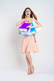 De mooie jonge vrouw in glazen op een lichte achtergrond houdt vele pakketten, het winkelen, koper Stock Foto's