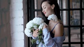 De mooie jonge vrouw in het overhemd en de bustehouder van mannen bevindt zich met een boeket van witte bloemen dichtbij het vens stock videobeelden