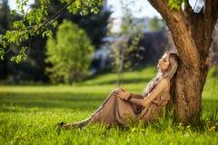 De mooie jonge vrouw kleedde zich in de zitting van de bohostijl op groene gra Stock Fotografie
