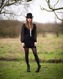 De mooie Jonge Vrouw kleedde zich in Zwarte Dragende Bowlingspelerhoed Stock Foto's
