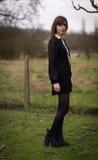 De mooie Jonge Vrouw kleedde zich in Zwarte op een Gebied stock foto