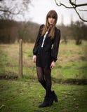 De mooie Jonge Vrouw kleedde zich in Zwarte op een Gebied stock fotografie
