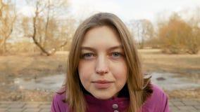 De mooie jonge vrouw komt en kijkt aan de camera stock videobeelden