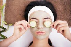 De mooie jonge vrouw krijgt gezichtskleimasker bij kuuroord, het liggen stock foto
