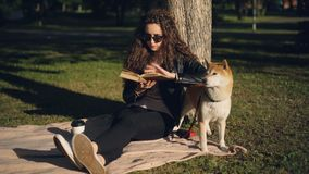 De mooie jonge vrouw leest boekzitting op deken onder boom in park en glimlacht terwijl haar rashond is stock videobeelden