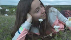 De mooie jonge vrouw ligt op een bloemweide in een grijze sweater Gelukkig meisje in aard in kleuren stock video