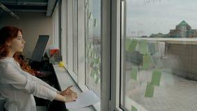 De mooie jonge vrouw lijmt stickers op venster die zich in modern bureau bevinden stock video