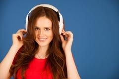 De mooie jonge vrouw luistert aan de muziek over trillende kleurenbac stock foto's
