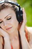 De mooie jonge vrouw luistert aan muziek in openlucht dragend hoofdtelefoons Stock Afbeeldingen