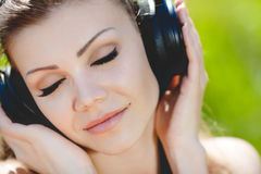 De mooie jonge vrouw luistert aan muziek in openlucht dragend hoofdtelefoons Stock Afbeelding