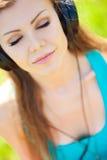 De mooie jonge vrouw luistert aan muziek in openlucht dragend hoofdtelefoons Royalty-vrije Stock Foto