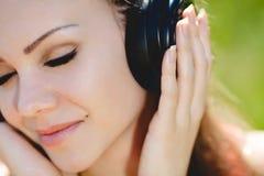 De mooie jonge vrouw luistert aan muziek in openlucht dragend hoofdtelefoons Stock Fotografie