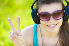 De mooie jonge vrouw luistert aan muziek in openlucht dragend hoofdtelefoons Royalty-vrije Stock Afbeeldingen