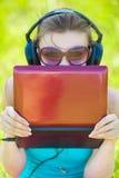 De mooie jonge vrouw luistert aan muziek in openlucht dragend hoofdtelefoons Stock Foto's