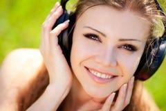 De mooie jonge vrouw luistert aan muziek in openlucht dragend hoofdtelefoons Royalty-vrije Stock Afbeelding