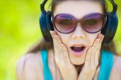 De mooie jonge vrouw luistert aan muziek in openlucht dragend hoofdtelefoons Stock Foto