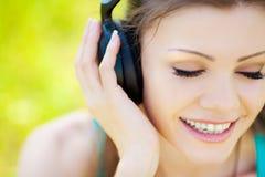 De mooie jonge vrouw luistert aan muziek in openlucht dragend hoofdtelefoons Royalty-vrije Stock Foto's