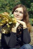 De mooie jonge vrouw met de herfst gaat in park weg royalty-vrije stock afbeeldingen