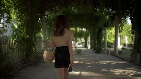 De mooie jonge vrouw met donker haar, die zwarte borrels en een beige t-shirt dragen loopt in het Park met een mand stock videobeelden