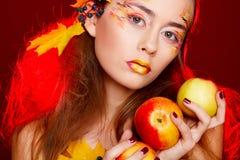 De mooie jonge vrouw met de herfst maakt over omhoog het stellen in studio stock afbeelding