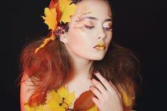 De mooie jonge vrouw met de herfst maakt over omhoog het stellen in studio stock fotografie