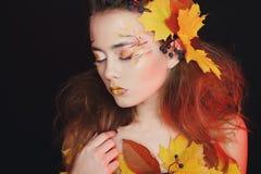 De mooie jonge vrouw met de herfst maakt over omhoog het stellen in studio stock afbeeldingen