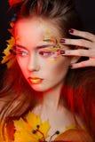 De mooie jonge vrouw met de herfst maakt over omhoog het stellen in studio royalty-vrije stock afbeeldingen