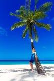 De mooie jonge vrouw met lang blond haar ontspant op de palm Stock Afbeelding