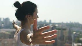 De mooie jonge vrouw met uit uitgerekt overhandigt het voelen van liefde aan het omringen van stad stock footage
