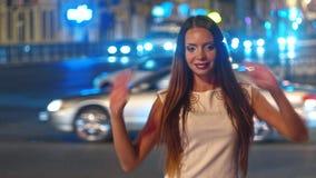 De mooie jonge vrouw in nachtstad toont overwinning en hartvormtekens aan camera met vage verkeerslichten stock video