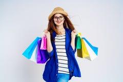 De mooie jonge vrouw op een lichte achtergrond die glazen dragen en een hoed dragen houdt pakketten, praal, glimlach, lege ruimte Stock Afbeeldingen