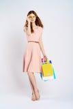 De mooie jonge vrouw op een lichte achtergrond in gele glazen houdt pakketten, het winkelen Royalty-vrije Stock Afbeeldingen