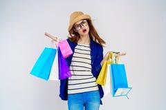 De mooie jonge vrouw op een witte achtergrond houdt pakketten in glazen, portret, het winkelen, koper Royalty-vrije Stock Afbeelding