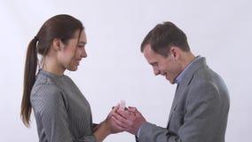 De mooie jonge vrouw opent een huidige doos voor een man en toont kerel haar huidige, mannelijke zeer gelukkig met giftomhelzing  stock video