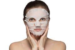 De mooie jonge vrouw past een kosmetisch masker op een gezicht op een witte achtergrond toe stock afbeeldingen