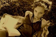 De mooie Jonge Vrouw is Readng een Boek in het park royalty-vrije stock foto