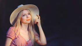 De mooie jonge vrouw in roze gestippelde de zomerkleding en zonhoed richt aan exemplaarruimte, bekijkend camera Drie - kwarten va stock afbeelding