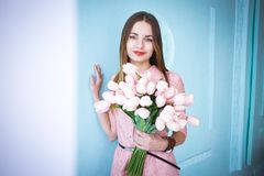 De mooie jonge vrouw in roze kledingsholding in de tulpen van de handenlente bloeit boeket op blauwe muurachtergrond stock foto's