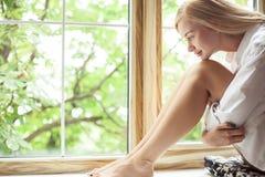 De mooie jonge vrouw rust dichtbij een venster Stock Afbeelding