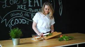 De mooie jonge vrouw snijdt groene komkommer met keukenmes op ronde stukken op houten scherpe raad en treft voorbereidingen stock videobeelden