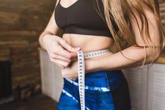 De mooie jonge vrouw in sportkleding meet de gemeten omtrek van de vluchttaille Sport, dieet en gewichtsverlies stock afbeeldingen
