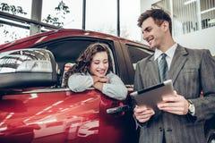 De mooie jonge vrouw spreekt aan knappe afdelingschef terwijl het kiezen van een auto in het handel drijven royalty-vrije stock fotografie