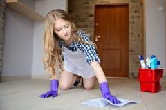 De mooie jonge vrouw wast de vloer op haar knieën royalty-vrije stock foto