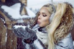 De mooie jonge vrouw in de winterkleding, die zich op de sneeuw bevinden en op de achtergrond heeft een mooie mening van de berge royalty-vrije stock fotografie