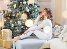 De mooie jonge vrouw in wit met grote Kerstmis stelt voor stock afbeeldingen
