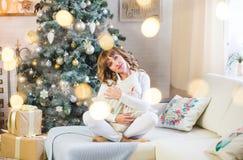 De mooie jonge vrouw in wit met grote Kerstmis stelt voor royalty-vrije stock fotografie